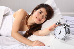 Beautiful woman in bed reaching for alarm clock Stock Photo