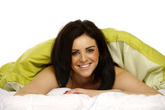 Beautiful woman in bed under a green duvet Royalty Free Stock Images