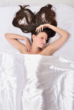 Beautiful woman  on the bed under white linen. Royalty Free Stock Images