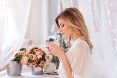 Beautiful woman in the bedroom drinking coffee. A girl holds Cup, enjoy a drink. Glamour portrait of beautiful woman model with fresh daily makeup and romantic stock image