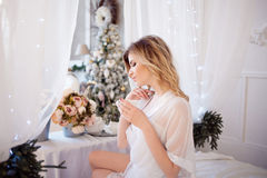 Beautiful woman in the bedroom drinking coffee. A girl holds Cup, enjoy a drink. Glamour portrait of beautiful woman model with fresh daily makeup and romantic royalty free stock photography