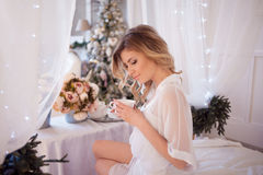 Beautiful woman in the bedroom drinking coffee. A girl holds Cup, enjoy a drink. Glamour portrait of beautiful woman model with fresh daily makeup and romantic stock photography