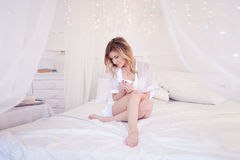 Beautiful woman in the bedroom drinking coffee. A girl holds  Cup, enjoy a drink. Square crop Royalty Free Stock Image