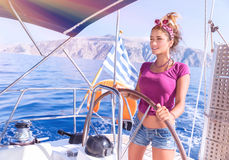 Beautiful woman behind helm of sailboat Stock Photography