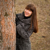 Beautiful woman behind the tree Royalty Free Stock Photo