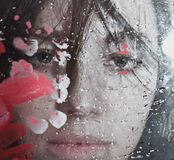 Beautiful woman behind wet glass Stock Photography