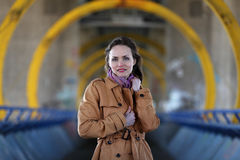 Beautiful woman in beige coat standing on a bridge. Young girl with brunette hair posing in front of industrial background royalty free stock photos