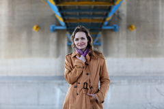 Beautiful woman with beige coat standing under a bridge. Young girl with brunette hair posing in front of industrial background Royalty Free Stock Images