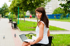 Beautiful woman on the bench. Portrait of a woman against the backdrop of the alley Stock Image
