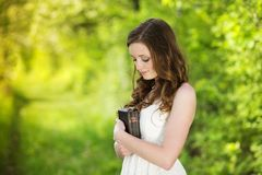 Beautiful woman with Bible. Is in sunny nature Royalty Free Stock Photos