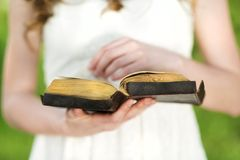 Beautiful woman with Bible. Is in sunny nature Royalty Free Stock Photo