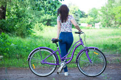 Beautiful woman with bicycle at the city park. Beautiful nature. Stock Images