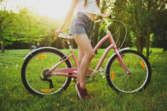 Beautiful woman with bicycle in the park stock photography