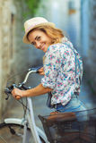 Beautiful woman with bicycle on street of old town Royalty Free Stock Image