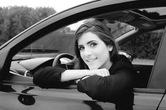 Beautiful woman with big eyes sitting in car smiling looking camera Stock Images