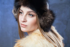 Beautiful woman in big fur hat and vest Royalty Free Stock Photos