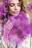 Beautiful woman among big purple flowers Stock Image