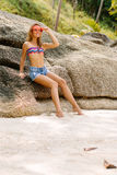 Beautiful woman on big stone in tropics. Stock Image