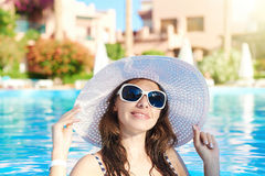 Beautiful woman in a big white hat on the background of the pool Royalty Free Stock Images