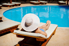 Beautiful woman in a big white hat on a lounger by the pool Royalty Free Stock Photos