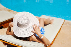 Beautiful woman in a big white hat on a lounger by the pool Royalty Free Stock Photo