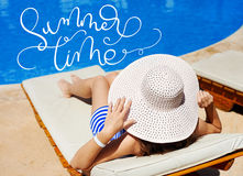 Beautiful woman in a big white hat on a lounger by the pool and text Summer time. Calligraphy lettering hand draw Stock Images