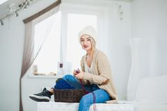 Beautiful woman in big white knitted hat indoors sit on chest with basket yarn. Stock Photos