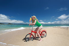 Beautiful woman on the bike on the beach Stock Image