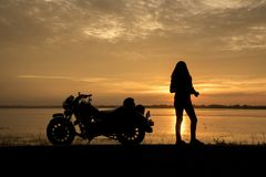 Beautiful Woman biker enjoying sunset, female riding motorcycle. motorbike driver traveling the world, Relaxing after long trip, f. Reedom lifestyle. Travel royalty free stock photo