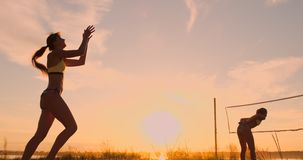 A beautiful woman in a bikini with a ball at sunset is getting ready to do serve jump on the beach in a volleyball match. On the sand. The decisive moment, the stock video