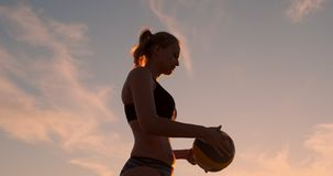 A beautiful woman in a bikini with a ball at sunset is getting ready to do serve jump on the beach in a volleyball match. On the sand. The decisive moment, the stock footage