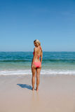 Beautiful woman in bikini at the beach. Rear view of beautiful woman wearing bikini at beach looking over shoulder. Young female in swimsuit standing on the royalty free stock photography