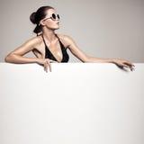 Beautiful woman in bikini holding big empty white billboard. Beautiful woman in black bikini holding big empty white billboard royalty free stock photo