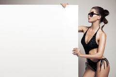 Beautiful woman in bikini holding big empty white billboard. Beautiful woman in black bikini holding big empty white billboard royalty free stock images