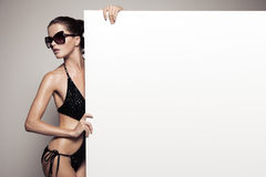 Beautiful woman in bikini holding big empty white billboard Royalty Free Stock Photography