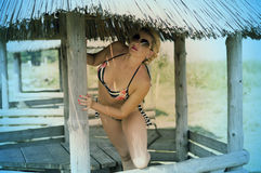 The beautiful woman in bikini looks out of an arbor. A subject summer holiday at the sea Stock Photo