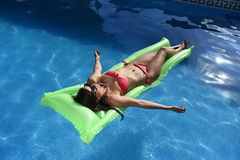Beautiful woman in bikini lying relax on float airbed at vacacti Stock Image