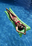 Beautiful woman in bikini lying relax on float airbed at vacation hotel resort swimming pool Stock Photos