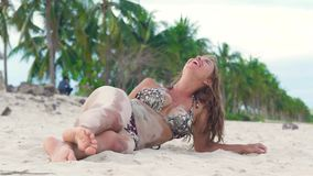 Beautiful woman in bikini lying on sandy beach and pouring sand on your body. woman strewing sand on her tanned. Body stock footage