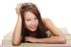 Beautiful woman in bikini lying on straw mat Stock Photography