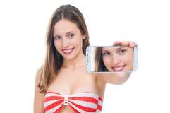 Beautiful woman in bikini making photo on the phone Stock Image