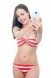 Beautiful woman in bikini making photo on the phone Royalty Free Stock Photography