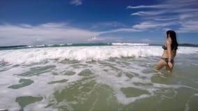 Beautiful woman in bikini in the ocean wave enters stock video