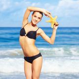 Beautiful woman in bikini. Portrait of young beautiful woman in black bikini with finger-fish on sea background royalty free stock image