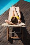 Beautiful woman in bikini relaxing by pool Stock Photography