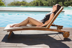 Beautiful woman in bikini relaxing by swimming pool Stock Image
