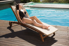 Beautiful woman in bikini relaxing by swimming pool Royalty Free Stock Images