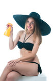 Beautiful woman in bikini sits with spray bottle. 