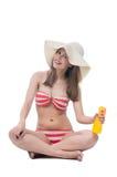 Beautiful woman in bikini sits with spray bottle Royalty Free Stock Photos