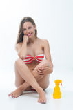 Beautiful woman in bikini sits with spray bottle Royalty Free Stock Images